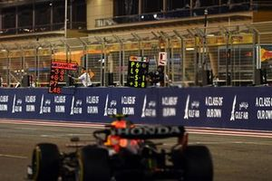 Sergio Perez, Red Bull Racing RB16B, passes the pit boards