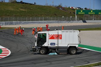 Marshals clear gravel from the track