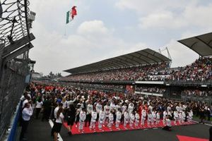 The drivers stand with the Grid Kid mascots during the national anthem as a helicopter flies the flag prior to the start