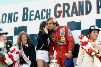 Podium: race winner Carlos Reutemann, Ferrari, with a kiss from Miss Long Beach Grand Prix, second place Mario Andretti, Lotus, third place Patrick Depailler, Tyrrell