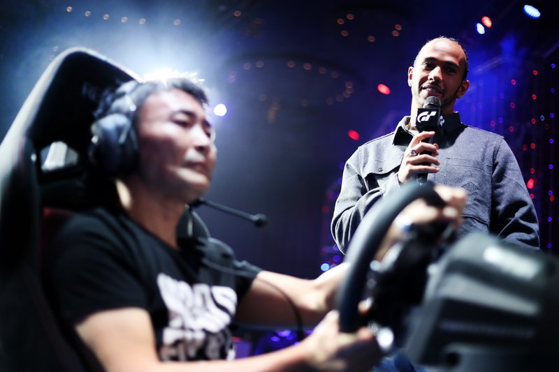 Formula 1 Driver, Lewis Hamilton looks on as producer of Gran Turismo, Kazunori Yamauchi gives a demonstration