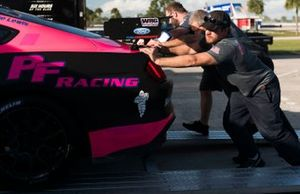 Team members push the #40 PF Racing Ford Mustang GT4: Jade Buford, James Pesek