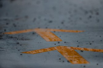 Rain falls on pit lane markings