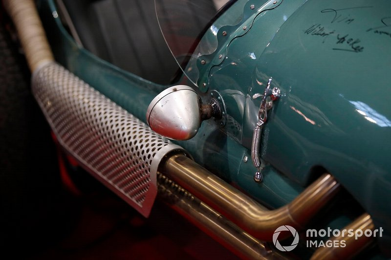 The wing mirror and exhaust pipes on a vintage Aston Martin race car