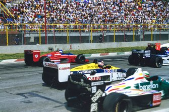 Nigel Mansell, Williams FW11 Honda, is passed by Patrick Tambay, Lola THL-2 Ford, and Teo Fabi, Benetton B186 BMW