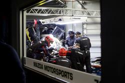 Mechanics working on the car of #70 Mazda Motorsports Mazda DPi: Joel Miller, Tom Long, James Hinchc