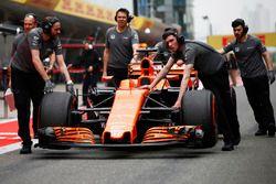Los miembros del equipo McLaren mueven el coche de Fernando Alonso, McLaren MCL32