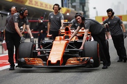 McLaren team members move the car of Fernando Alonso, McLaren MCL32