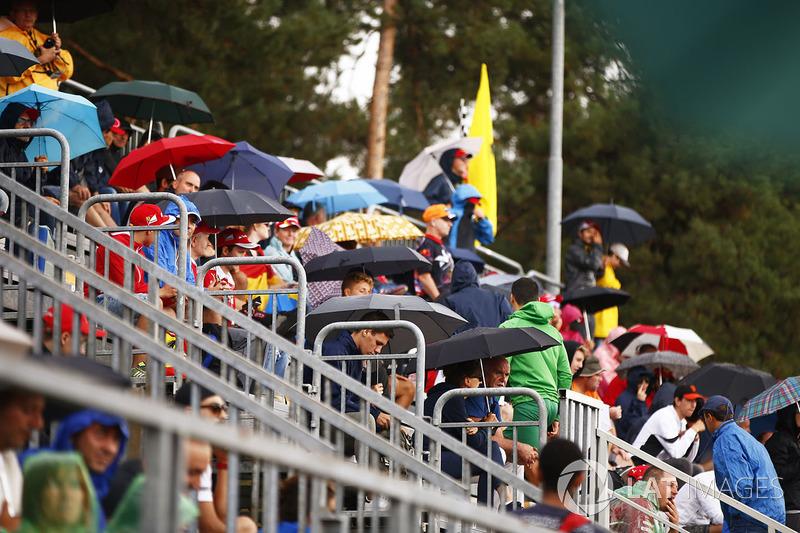 Para penonton berusaha berlindung dari hujan