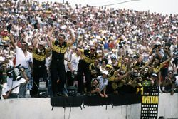 The Lotus team celebrate as Ayrton Senna, Lotus 98T Renault, crosses the line to claim victory