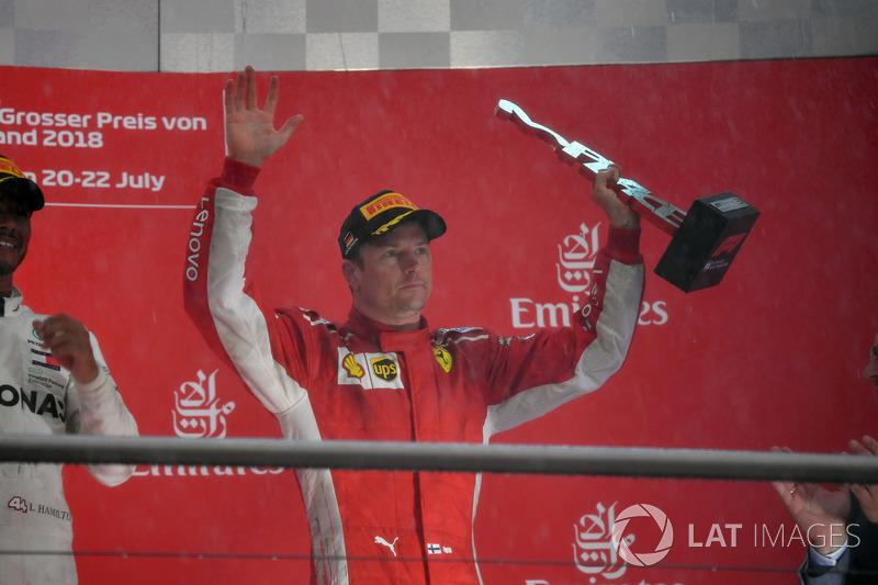 Kimi Raikkonen, Ferrari, celebrates on the podium with the trophy