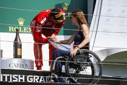 Derde Kimi Raikkonen, Ferrari, krijgt trofee van Nathalie McGoin op het podium