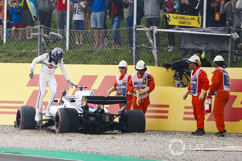 Lance Stroll, Williams Racing, climbs out of his car after spinning into the gravel