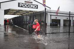 A young fan runs through the rain puddles in the Pocono Raceway paddock