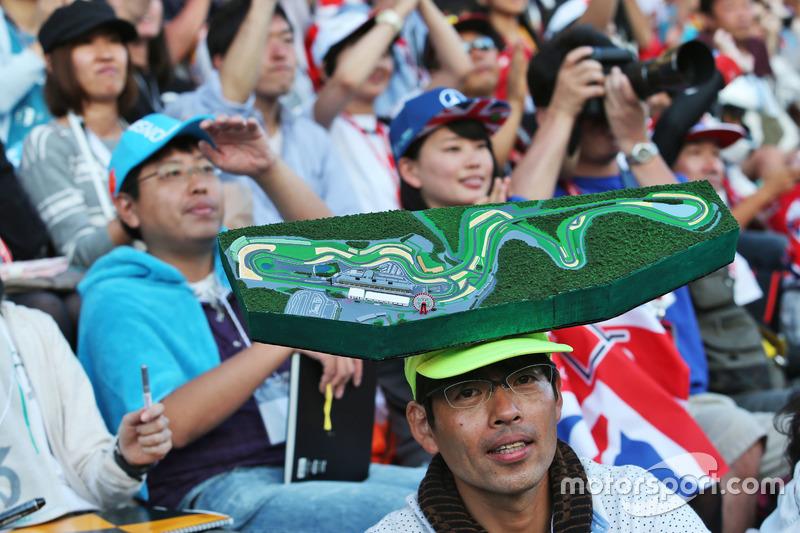 Fans en la tribuna con el mapa del circuito en la cabeza