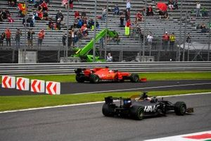 Romain Grosjean, Haas F1 Team VF-19, passes as Sebastian Vettel, Ferrari SF90, rejoins from a run-off area
