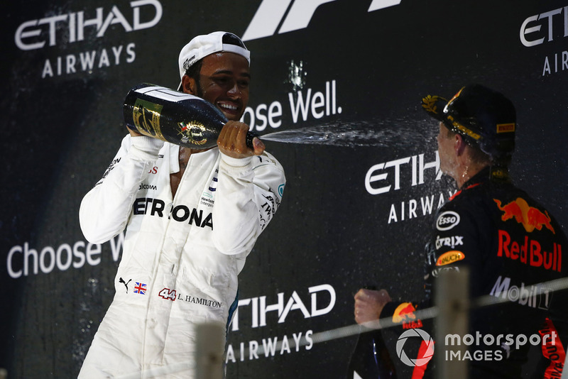 Lewis Hamilton, Mercedes AMG F1, 1st position, sprays Max Verstappen, Red Bull Racing, 3rd position, with Rose Water on the podium