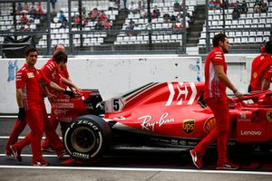 Ferrari engineers move the car of Sebastian Vettel, Ferrari SF71H, in the pit lane