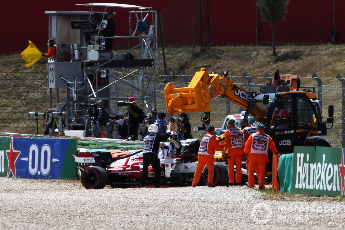 Los oficiales de pista trabajan para recuperar el coche de Kimi Raikkonen, Alfa Romeo Racing C41