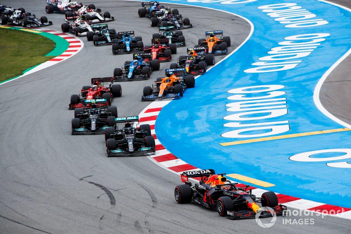 Max Verstappen, Red Bull Racing RB16B, Lewis Hamilton, Mercedes W12, Valtteri Bottas, Mercedes W12, Daniel Ricciardo, McLaren MCL35M, Charles Leclerc, Ferrari SF21, y el resto del pelotón en la primera vuelta