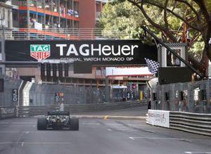 Sebastian Vettel, Aston Martin AMR21, crosses the line as Serena Williams waves the chequered flag