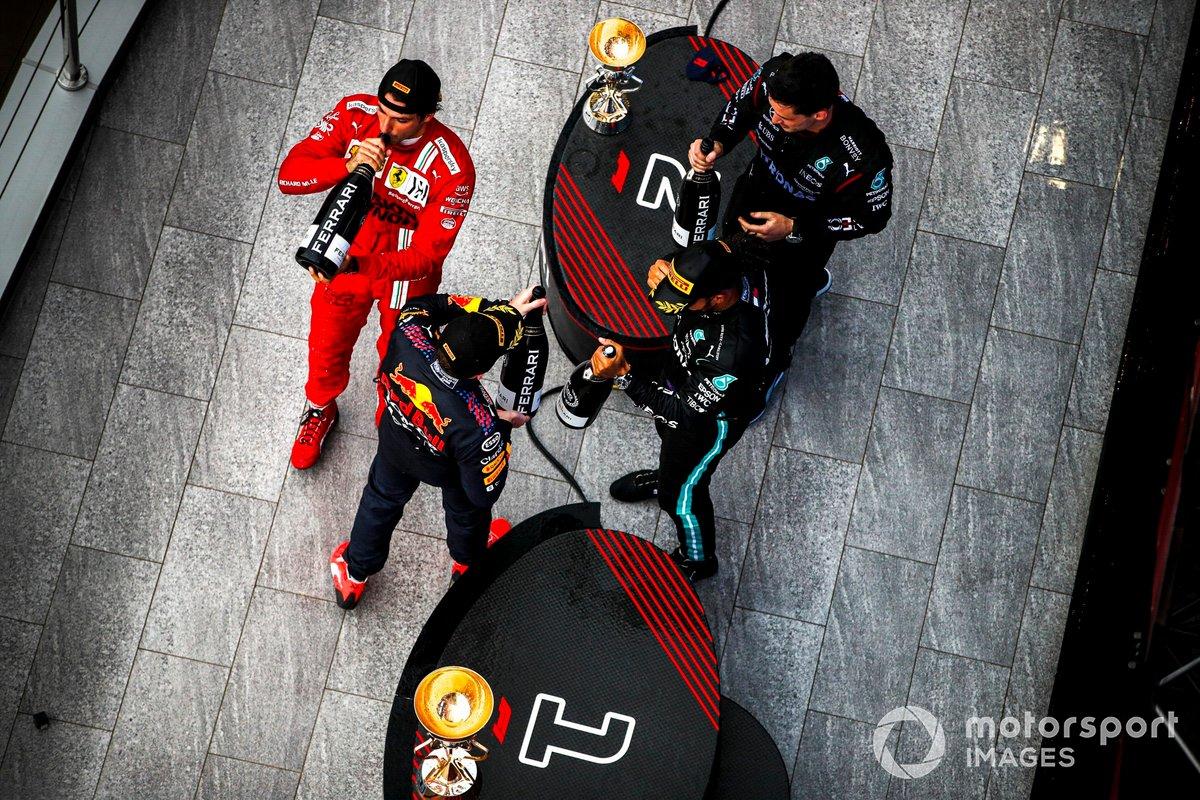 Max Verstappen, Red Bull Racing, 2a posizione, Carlos Sainz Jr., Ferrari, 3a posizione, il rappresentante del team Mercedes e Lewis Hamilton, Mercedes, 1a posizione, con Champagne sul podio