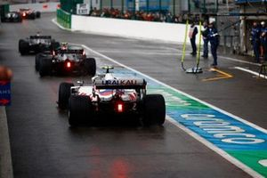 Lewis Hamilton, Mercedes W12, Valtteri Bottas, Mercedes W12, and Mick Schumacher, Haas VF-21, queued to leave the pits