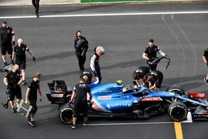 Esteban Ocon, Alpine F1, and Alpine F1 mechanics gather around their car after technical issues cause a stop on the grid at the end of FP2