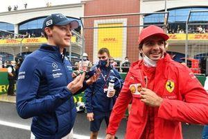 George Russell, Williams, en Carlos Sainz Jr., Ferrari, praten op de grid