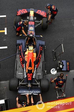 The Alexander Albon Red Bull Racing RB16 is wheeled into the garage by mechanics