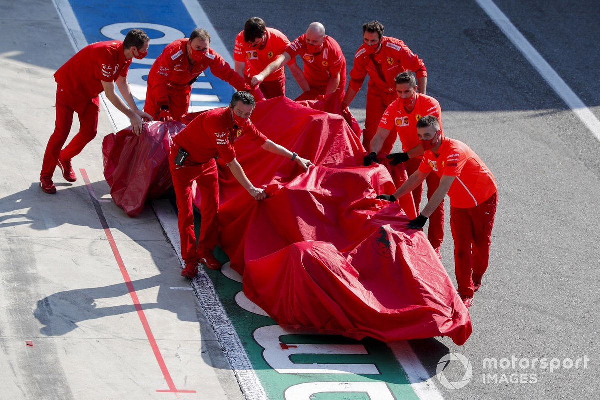 El monoplaza de Charles Leclerc, el Ferrari SF1000 es devuelto al garaje por los mecánicos de Ferrari