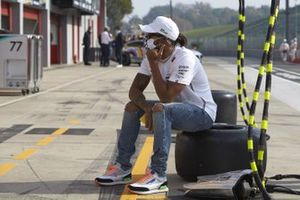 Lewis Hamilton, Mercedes-AMG F1, sits on a tyre in the pit lane