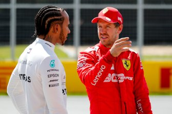 Front row starters Lewis Hamilton, Mercedes AMG F1, and pole man Sebastian Vettel, Ferrari, talk after Qualifying
