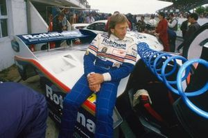 Derek Bell, Porsche 962C, relaxes on his car in the pits before the race