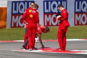 Sebastian Vettel, Ferrari, inspects a kerb