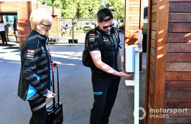 Imembri del Team Williams usano l' igienizzante per le mani prima di entrare in pista