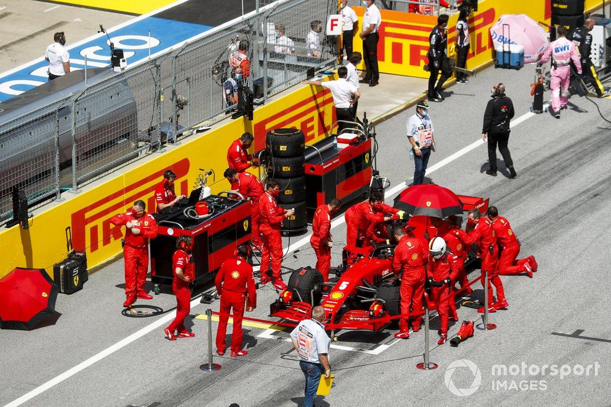 Meccanici e ingegneri Ferrari preparano l'auto di Sebastian Vettel, Ferrari SF1000, sulla griglia di partenza
