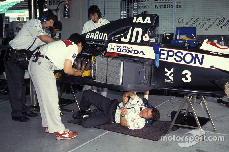 Mechanics work on Satoru Nakajima's Tyrrell 020 Honda in the garage