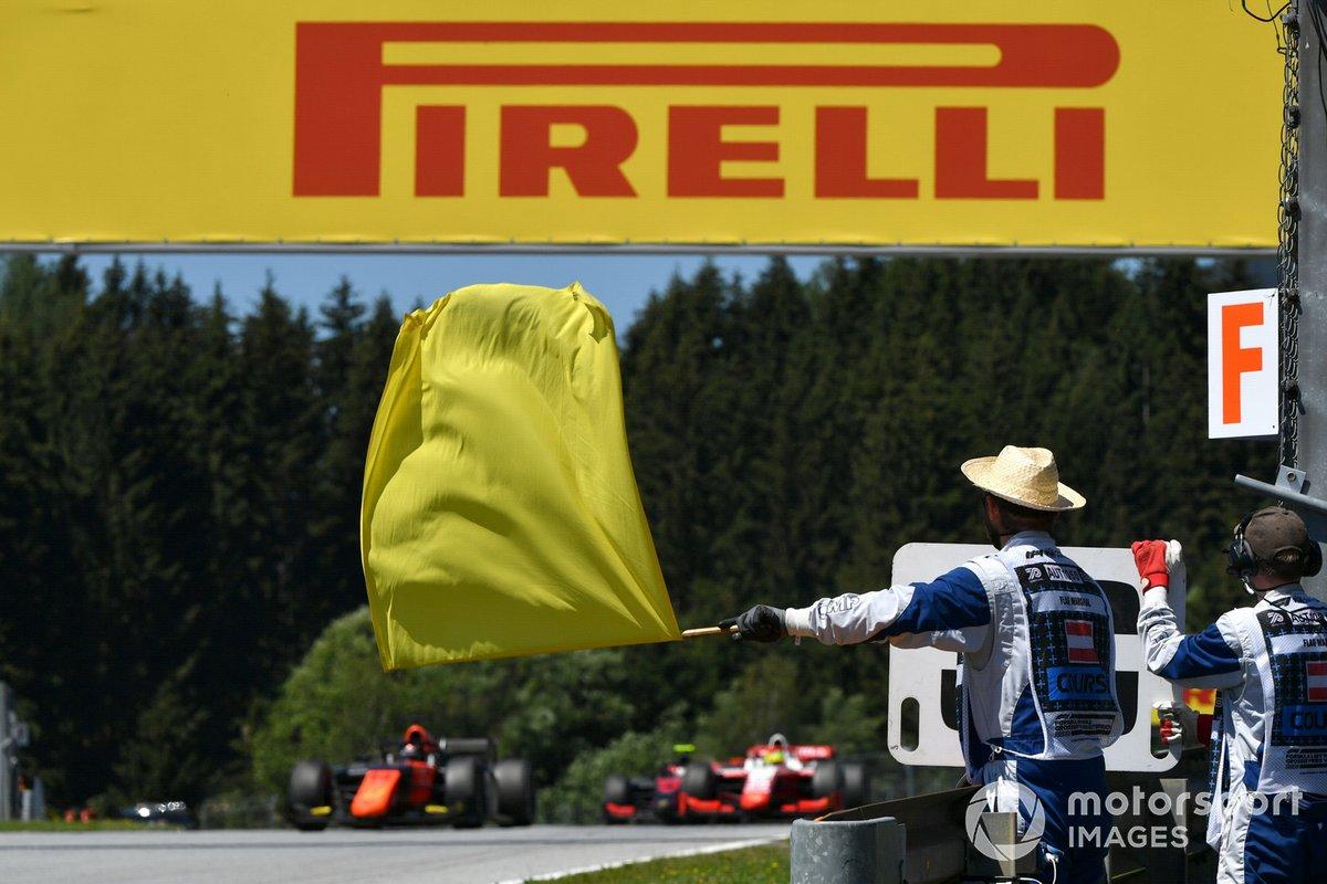 Un comisario con la bandera amarilla con Nobuharu Matsushita, MP Motorsport, al fondo
