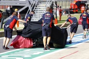 Red Bull mechanics return the damaged car of Alex Albon, Red Bull Racing RB16, to the garage under a tarpaulin, after his crash in FP2