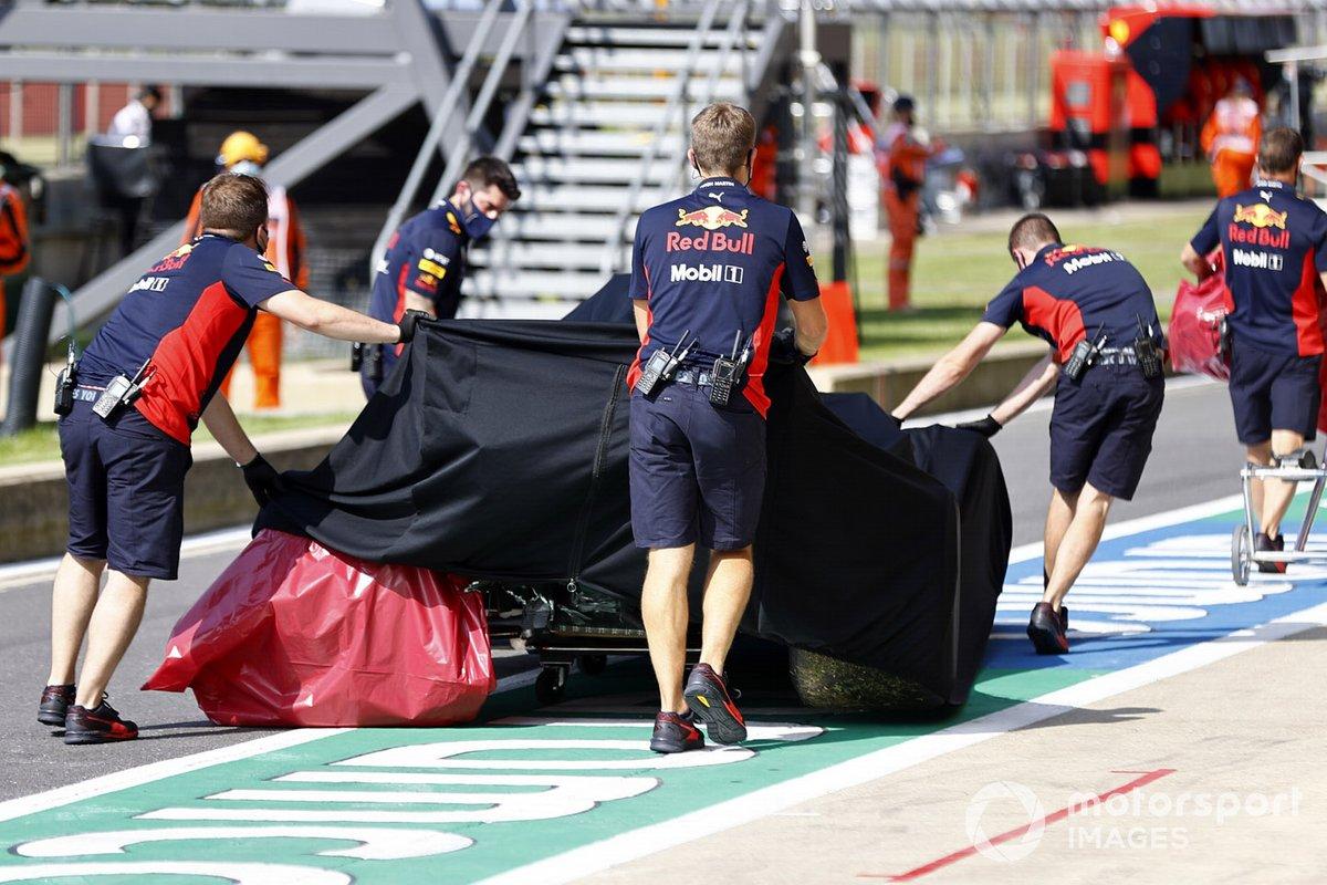 Los mecánicos de Red Bull con el monoplaza dañado de Alex Albon, Red Bull Racing RB16 en el garaje bajo una lona después de su accidente en la FP2