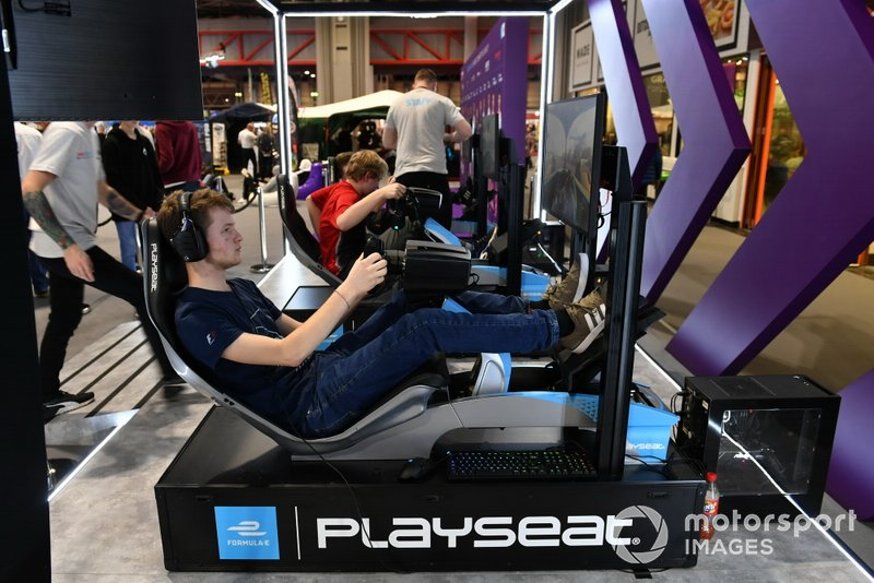 A fan tries one of the simulator rigs on the Formula E stand