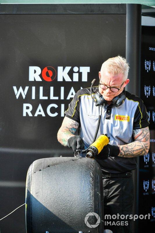 Pirelli team member cleans tyres