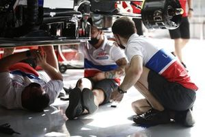 Haas F1 mechanics work on their cars in the garage
