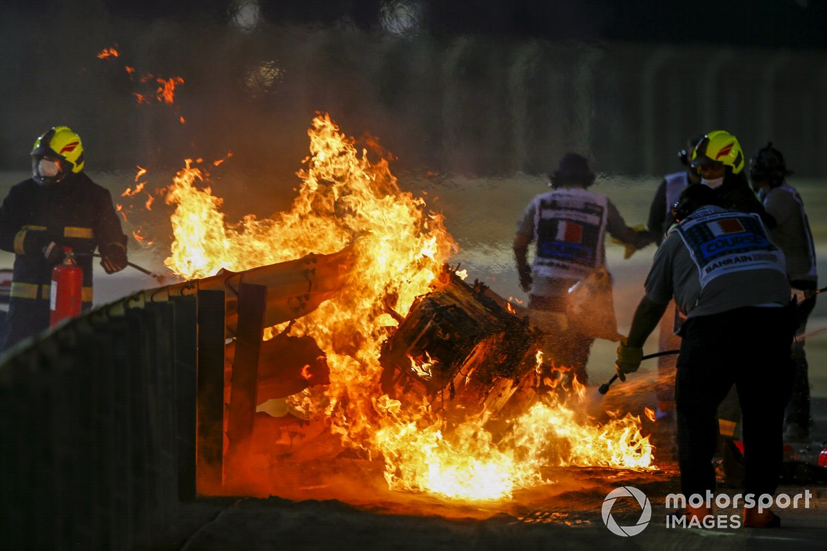 Fire marshals deal with the flames after a huge crash for Romain Grosjean, Haas VF-20, on the opening lap