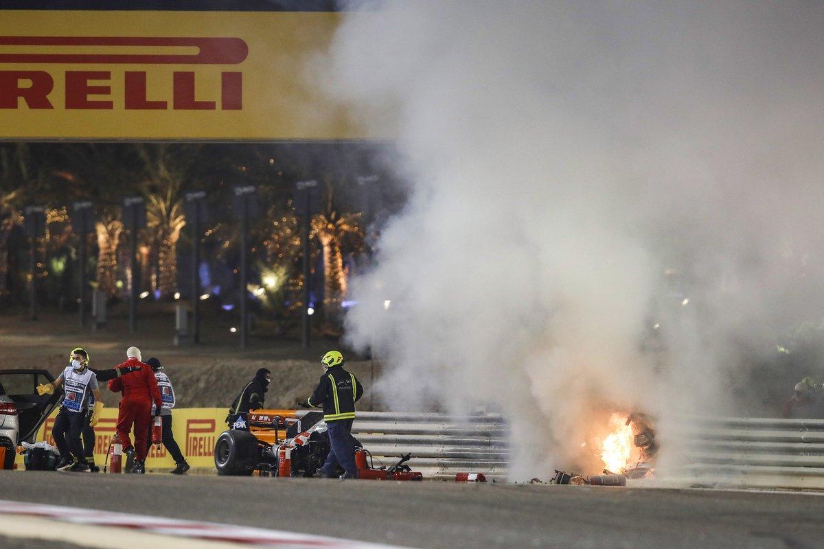 Los oficiales de pista trabajan para apagar el fuego en la escena del accidente