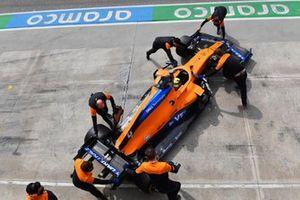 Lando Norris, McLaren MCL35M, is returned to the garage