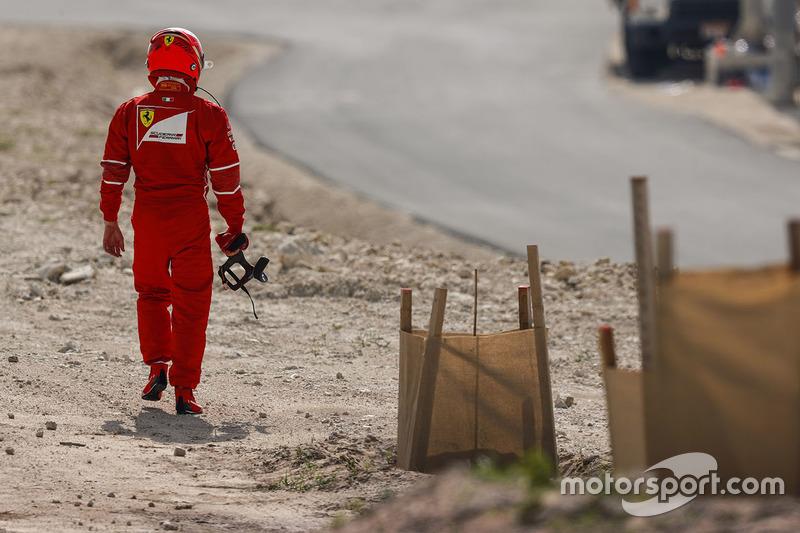 Кими Райкконен идет в боксы после остановки на трассе во время тренировки Гран При Бахрейна
