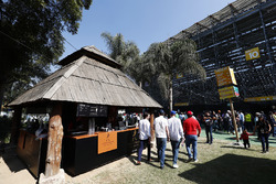 Fans walk past a Johnnie Walker-branded bar behind a grandstand
