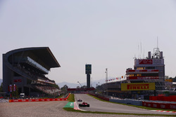 A Ferrari follows a Force India onto the pit straight